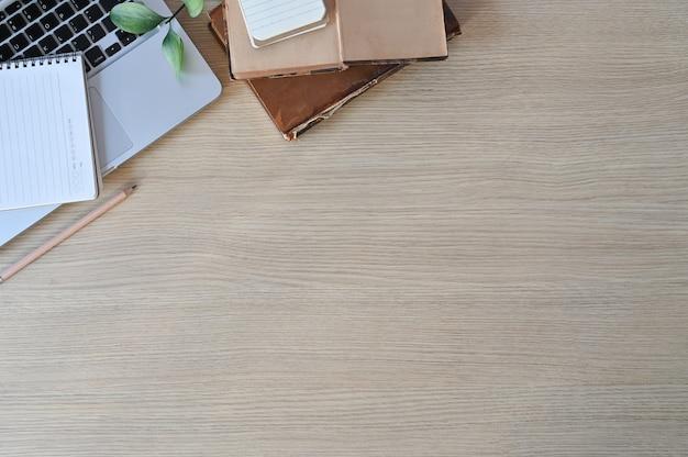 Bureau en bois avec ordinateur portable, livres et crayon dans l'espace de copie vue de dessus.