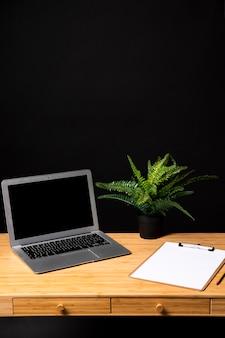Bureau en bois simple avec presse-papiers et ordinateur portable