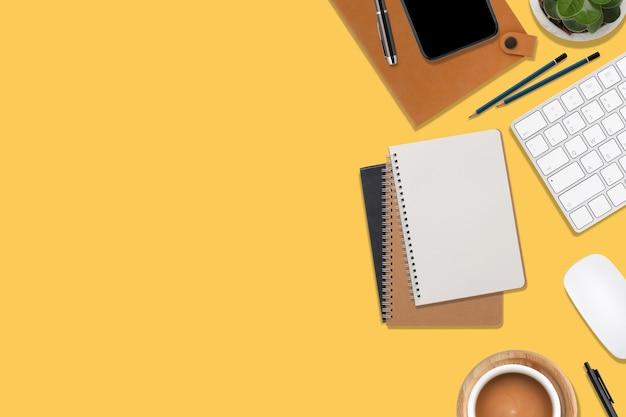 Bureau de bureau en bois jaune vue de dessus avec ordinateur et fournitures de bureau.
