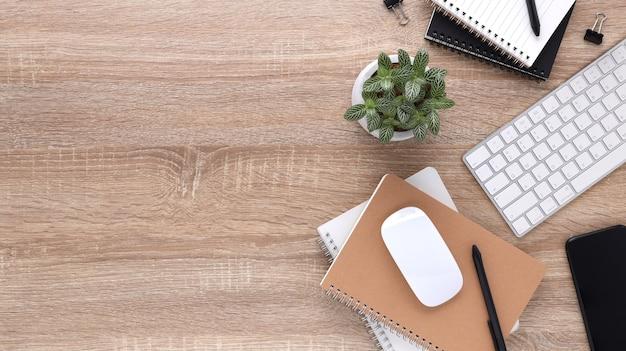 Bureau de bureau en bois vue de dessus avec ordinateur et fournitures de bureau.