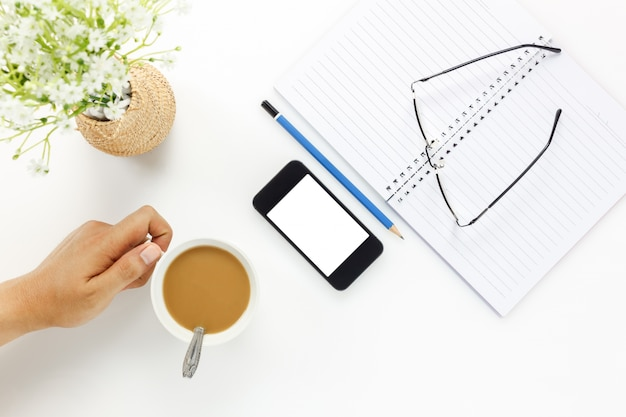 Bureau de bureau de bureau de dessus de bureau. homme d'affaires qui touche une tasse de café et un téléphone portable, des lunettes, un café, un cahier, un crayon, une belle fleur blanche sur un bureau de bureau blanc avec un espace de copie.