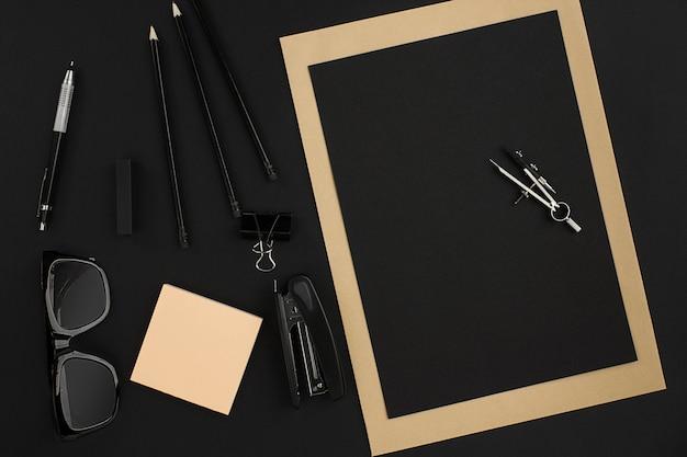 Bureau de bureau avec divers objets noirs sur fond noir. vue de dessus. nature morte