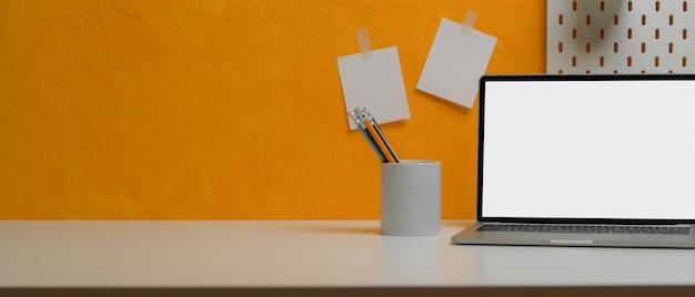 Bureau de bureau à domicile créatif avec ordinateur portable, papeterie, espace copie et bloc-notes sur mur jaune