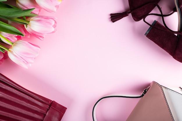 Bureau de bureau à domicile féminin. espace de travail avec cahier, fleurs de tulipes roses et accessoires. mise à plat, vue de dessus. fond de blog de mode. les femmes platement. concept de mode.