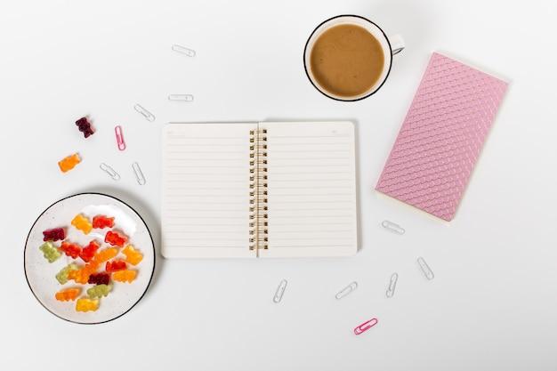 Bureau de bureau à domicile plat. bloc-notes, trombones, crayon, café et bonbons