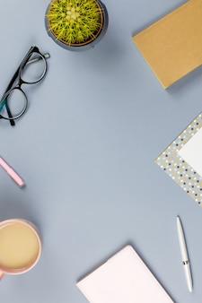 Bureau de bureau à domicile plat. espace de travail féminin avec carnet de notes, lunettes, tasse à thé, journal intime, plante. espace copie