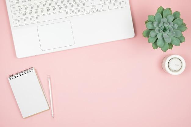 Bureau de bureau à domicile plat. espace de travail des femmes avec ordinateur portable, ordinateur portable, stylo sur une surface rose. surface féminine vue de dessus.