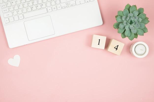 Bureau de bureau à domicile plat. espace de travail pour femmes avec ordinateur portable et décoration sur surface rose. concept de la saint-valentin