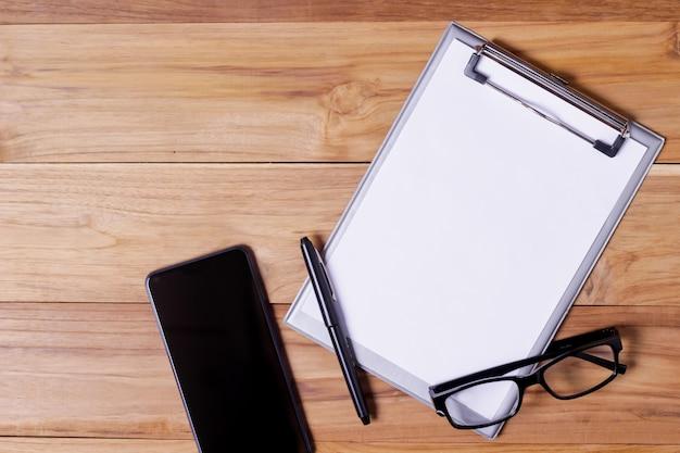 Bureau de bureau avec lunettes, bloc-notes court, stylo et smartphone.