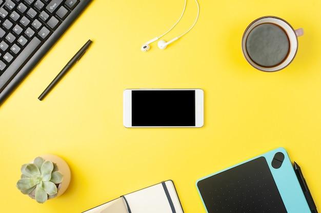 Bureau de bureau minimal. mise à plat - maquette de smartphone, clavier, écouteurs, tablette sur fond jaune. vue de dessus. concept de lieu de travail. place pour le texte.