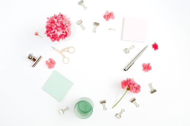 Bureau de bureau de mode plat laïque. espace de travail cadre féminin avec fleurs rouges, accessoires, journal à la menthe sur blanc