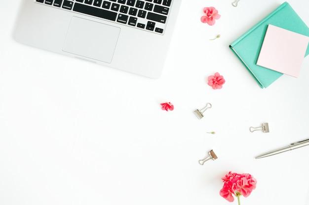 Bureau de bureau de mode plat laïque. espace de travail féminin avec ordinateur portable, fleurs rouges, accessoires, agenda à la menthe sur blanc