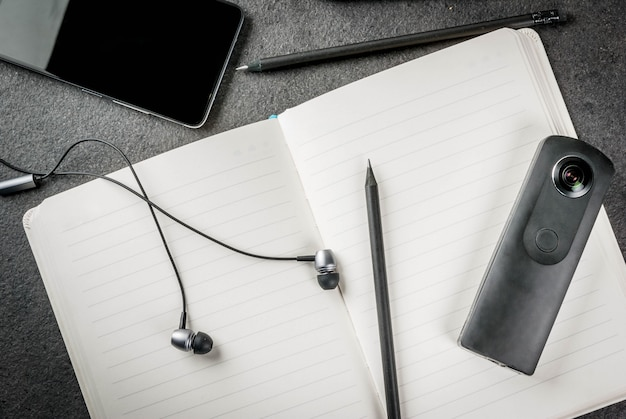 Bureau, bureau noir avec électroménagers. . bloc-notes, stylos pour appareils photo panoramiques (crayons), smartphone et casque sur la table.