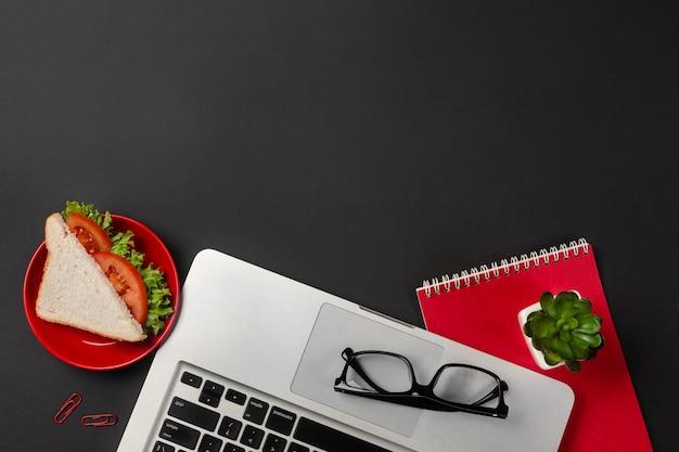 Bureau de bureau noir élégant avec ordinateur portable, tasse de café et un sandwich pour le déjeuner. vue de dessus
