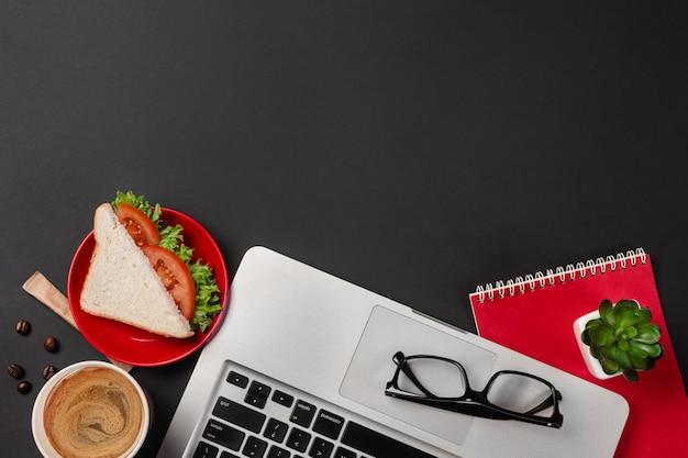 Bureau de bureau noir élégant avec ordinateur portable, tasse de café et un sandwich pour le déjeuner en vue de dessus