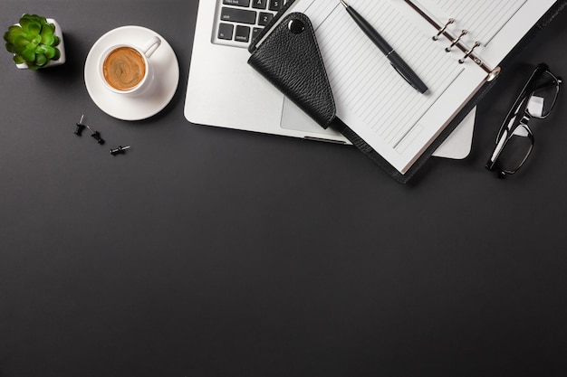 Bureau de bureau noir élégant avec ordinateur portable et tasse de café en vue de dessus