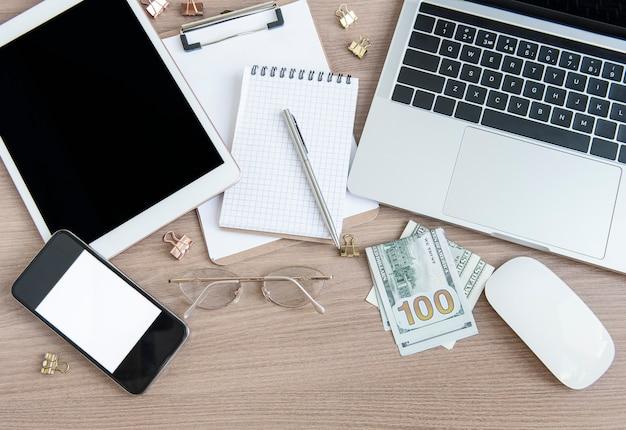 Bureau de bureau. ordinateur portable avec fournitures de bureau et argent sur la table.