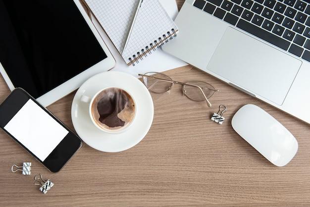 Bureau de bureau. ordinateur portable avec fournitures de bureau et café sur la table.
