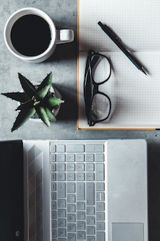 Le bureau bureau plat vue avec ordinateur portable, souris, arbre, trombone, tasse à café, cahier, crayon, lunettes noires sur fond blanc.