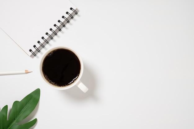 Bureau avec cahier vierge et tasse de café sur la vue de dessus de fond blanc.