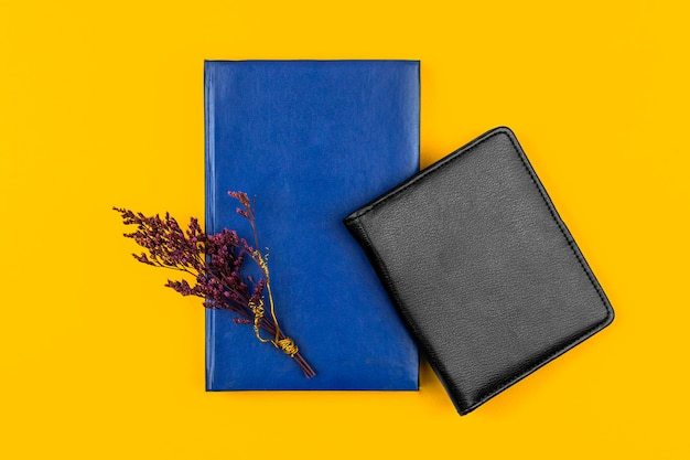 Bureau avec cahiers en cuir, composition d'entreprise avec fond jaune et fleur séchée, photo vue de dessus
