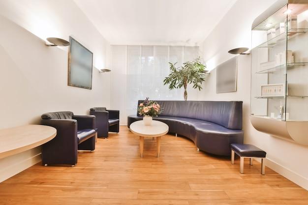 Bureau et chaise modernes situés dans un bureau à domicile spacieux avec des murs blancs dans une maison lumineuse