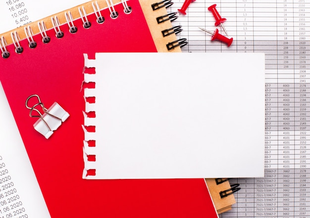 Le bureau comporte des blocs-notes marron et rouge, des rapports, des boutons rouges et une feuille de papier blanche avec un espace pour insérer du texte ou des illustrations. modèle. concept d'entreprise