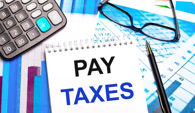 Le bureau contient des tableaux colorés, une calculatrice, des lunettes, un stylo et un cahier avec le texte pay taxes