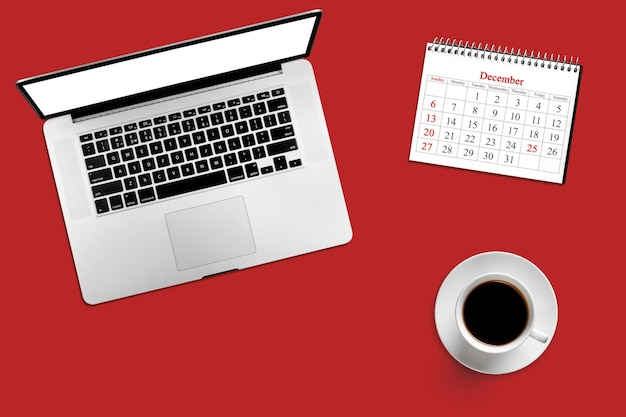 Bureau couleur avec ordinateur, café et calendrier pour le 25 décembre