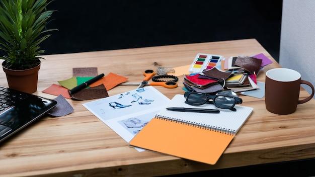 Bureau de créateur de mode. espace de travail d'entreprise contemporain. échantillons de couleur, bloc-notes et fournitures sur la table