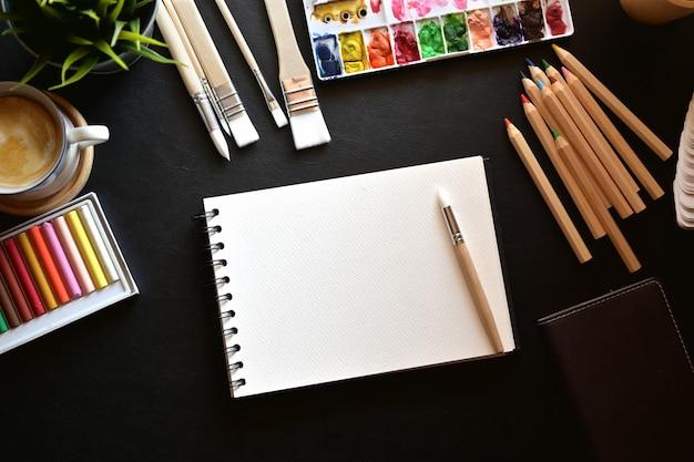 Bureau en cuir d'artiste avec fournitures créatives et espace de copie.