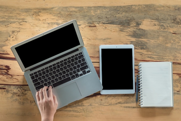 Un bureau dans un bureau avec un ordinateur portable, il écrit un blog. les mains des hommes sur le clavier.
