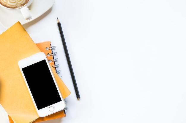 Bureau dans la vue de dessus de bureau. crayon avec ordinateur portable et smartphone avec café sur isolé