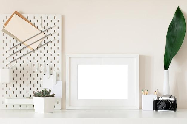 Bureau à domicile blanc avec cadre photo, fournitures, fleur. conception de maquette de cadre vierge minimale.
