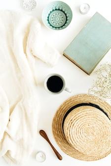 Bureau à domicile avec café, livre, chapeau de paille et couverture sur une surface blanche