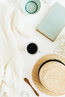Bureau à domicile avec café, livre, chapeau de paille, fleurs et couverture sur une surface blanche