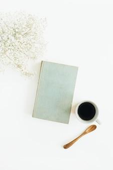 Bureau à domicile avec café, livre, fleurs sur une surface blanche