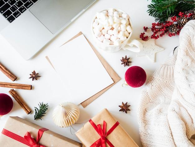 Bureau à domicile avec décorations de noël, carte postale avec enveloppe, tasse avec boisson chaude avec guimauves, cadeaux, pull en tricot et épices. vue de dessus,