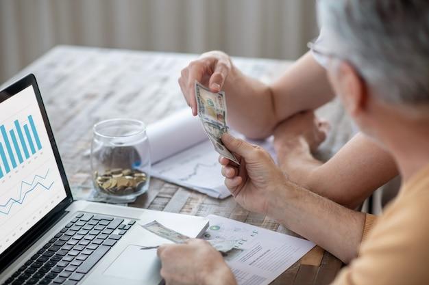 Bureau à domicile. deux hommes assis à la table et travaillant sur un ordinateur portable