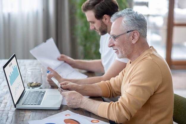Bureau à domicile. deux hommes travaillant dans un bureau à domicile et semblant impliqués