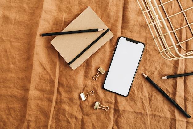 Bureau à domicile avec téléphone intelligent écran maquette sur couverture marron. mise à plat, vue de dessus