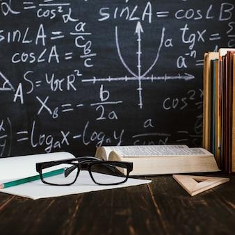Bureau d'école dans la salle de classe, avec des livres sur fond de tableau avec des formules écrites