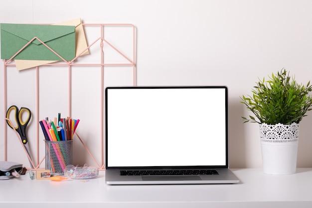 Bureau d'école dans un style moderne avec ordinateur portable sur fond blanc. éducation à domicile. décor moderne. maquette.