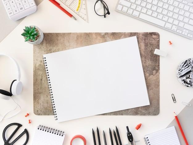 Bureau d'école avec feuille de papier, fournitures pour étudiants et clavier d'ordinateur sur le bureau