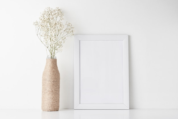 Bureau d'espace de travail avec cadre vide et fleur dans un vase