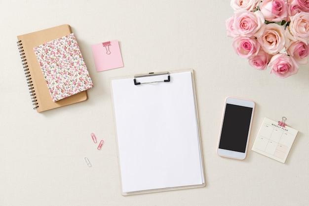 Bureau féminin avec bouquet de roses roses, agenda rose sur blanc. mise à plat. vue de dessus féminine