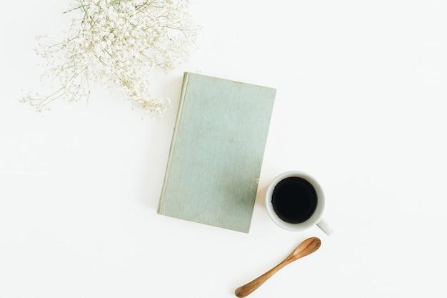 Bureau féminin avec café, livre, fleurs sur une surface blanche