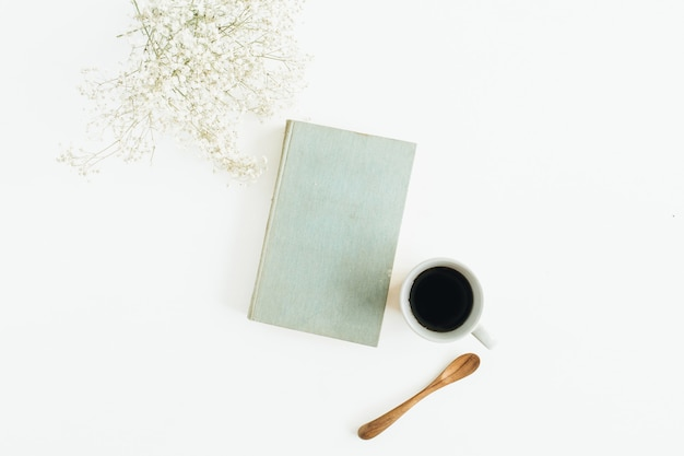 Bureau féminin avec café, livre, fleurs sur surface blanche