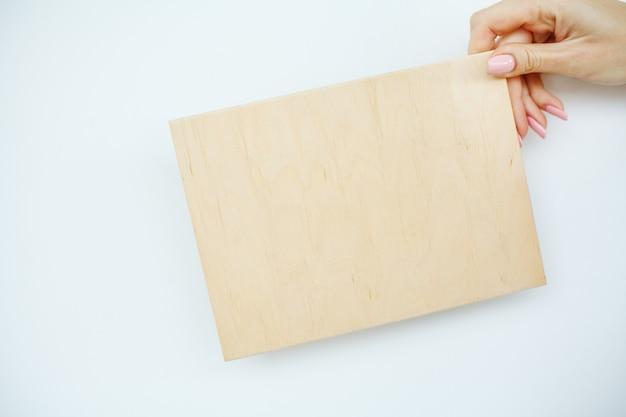 Bureau femme mains tenant une planche d'arbre sur fond blanc