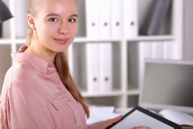 Bureau de fille capable dans l'ordinateur portable avant tient la tablette